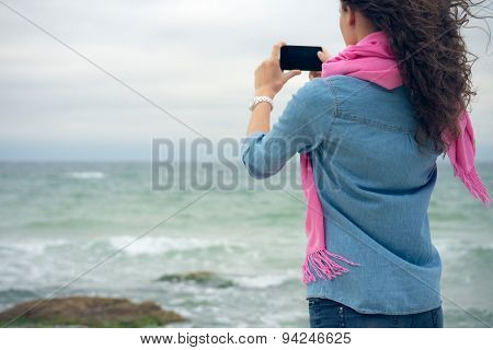 Young Woman With Curly Hair In Denim Clothes Takes A Picture Of The Ocean