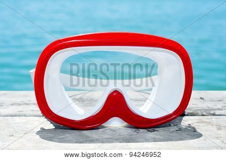 closeup of a red and white diving mask on an old wooden pier above the sea