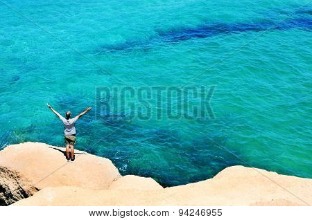 a young man with the arms in the air in front of the ocean, feeling free
