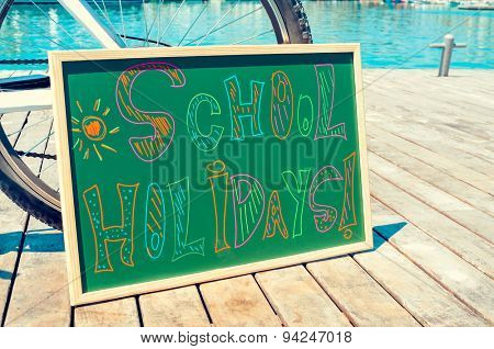 the text school holidays written with chalk of different colors in a chalkboard, on a wooden pier on the sea
