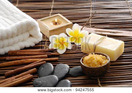 Two frangipani and cinnamon, black stones,towel on mat