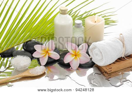 Spa set with salt in spoon, towel, candle ,oil, orchid ,stones â??green palm background