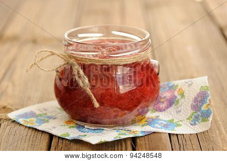 Homemade Strawberry Jam In Open Glass Jar With Hempstring On Paper Napkin