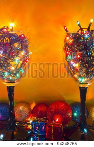 Glasses With A Yellow Background Garlands With Christmas Toys And Gifts
