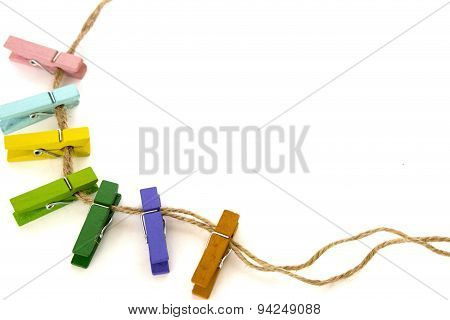 Colored Clothespins On A Rope Isolated On White Background