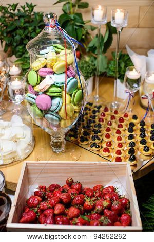 Table with desserts - macaroons, strawberry, cookies