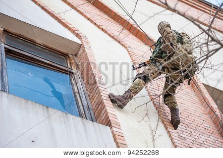 Soldiers in camouflage climbing a building wall
