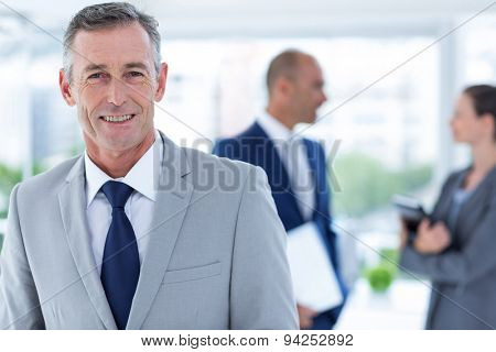 businessman smiling with two colleague behind him at the office
