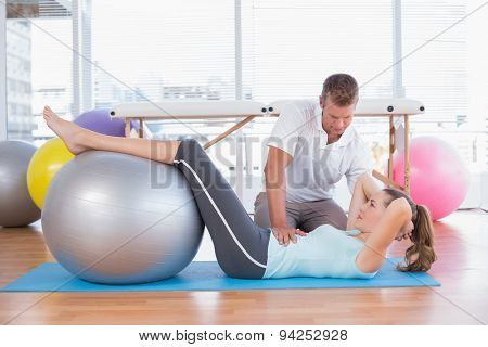 Trainer working with woman on exercise mat in fitness studio