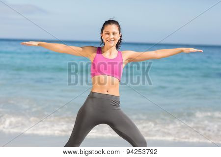 Fit woman doing fitness beside the sea at the beach