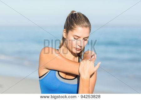 Beautiful fit woman stretching her arm at the beach