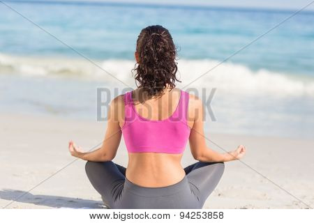 Wear view of fit woman doing yoga beside the sea at the beach