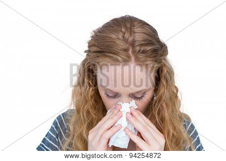Sick blonde woman blowing her nose on white background