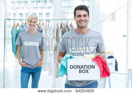 Happy volunteer man holding a donation box