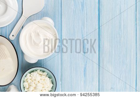 Dairy products on wooden table. Sour cream, milk, cheese and yogurt. Top view with copy space