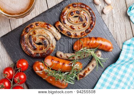 Grilled sausages and beer mug on wooden table. Top view