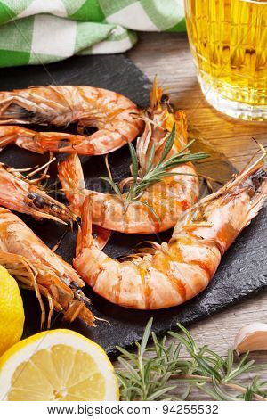 Grilled shrimps on stone plate and beer mug on wooden table