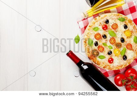 Italian pizza with cheese, tomatoes, olives, basil and red wine on wooden table. Top view with copy space