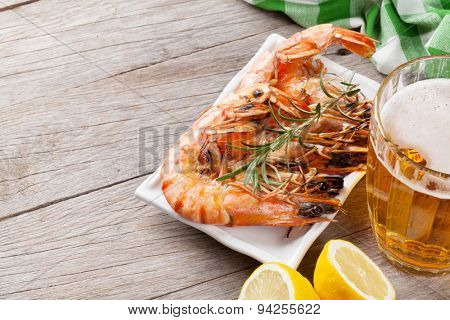 Beer mug and grilled shrimps on wooden table. View with copy space