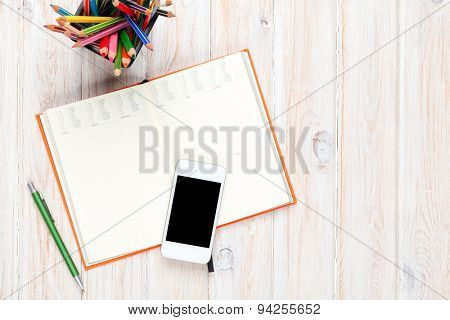 Office desk table with notepad and colorful pencils. Top view