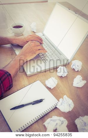Active hands typing on a laptop with paper pellets beside