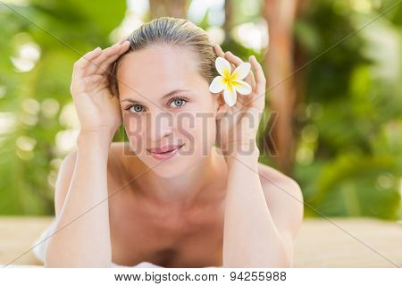 Peaceful blonde lying on towel with candle at the health spa