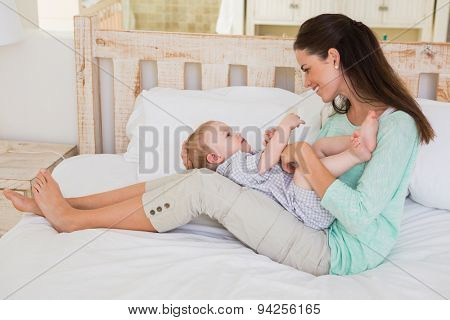 Happy mother with her baby boy at home in bedroom