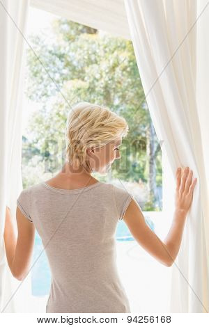 Pretty blonde woman look outside at home