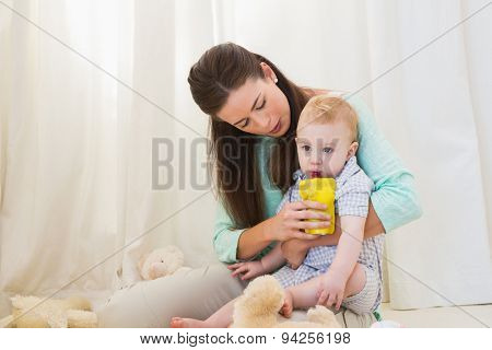 Mother and baby sitting on floor at home