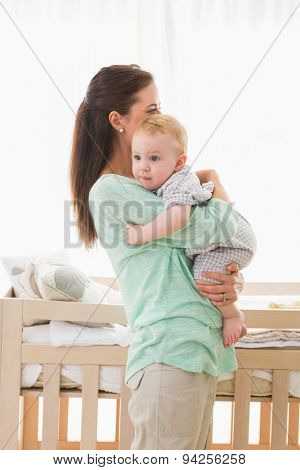 Happy mother holding baby boy at home in bedroom