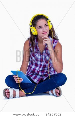 Thoughtful pretty brunette listening music with her tablet computer on white background