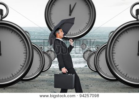 Businessman pushing the wind with umbrella against cloudy landscape background