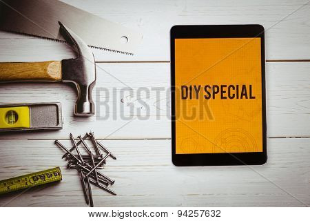 The word diy special and tablet pc against architecture themed background