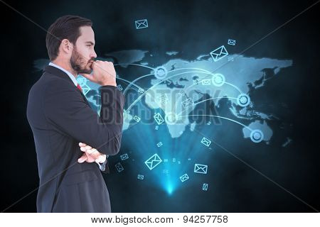 Thinking businessman standing with hand on chin against futuristic technology interface