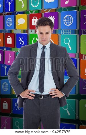 Serious businessman with hands on hips against green background with vignette