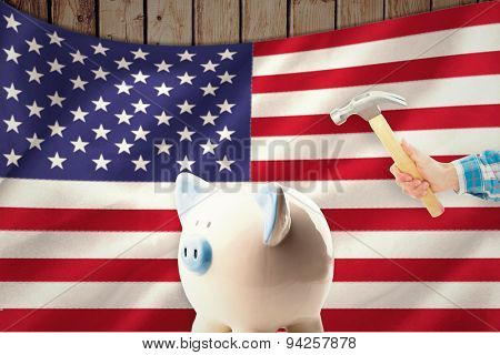 hand holding hammer against digitally generated american national flag