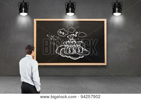 Thinking businessman touching his chin against blackboard with copy space