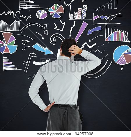Thoughtful businessman with hand on head against blackboard