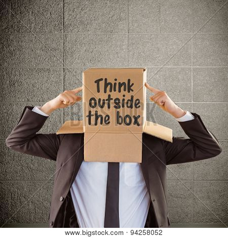 Anonymous businessman pointing to box against grey room