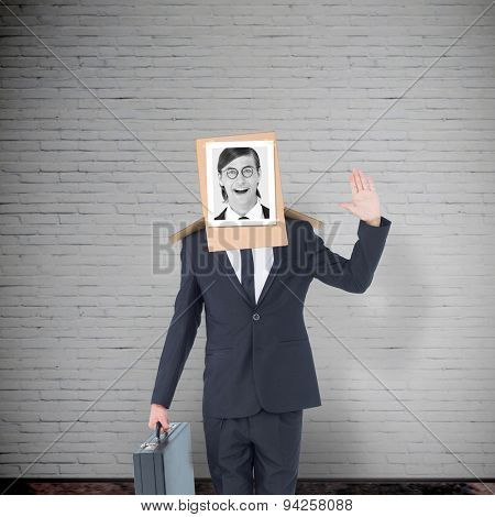 Businessman with photo box on head against grey room