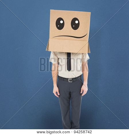 Businessman standing with box on head against blue background