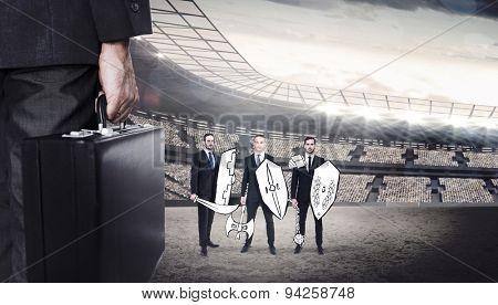 Businessman holding briefcase against stadium