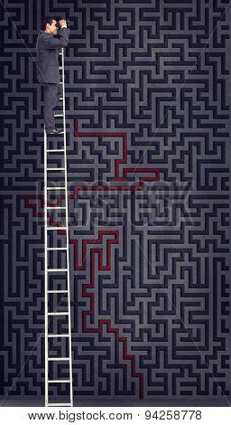 Businessman standing on ladder using binoculars against maze