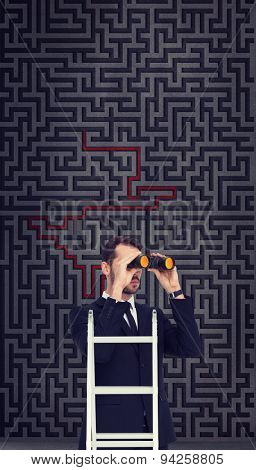 Businessman looking on a ladder against maze