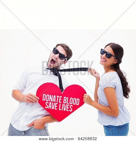 Brunette pulling her boyfriend by the tie holding heart against donate blood save lives