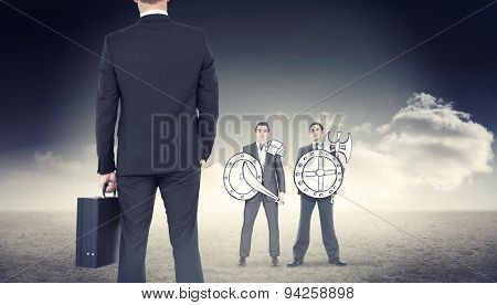 Businessman standing with his briefcase against desert landscape
