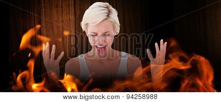Angry blonde yelling with hands up against wooden table