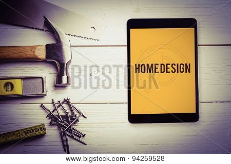 The word home design and tablet pc against blueprint