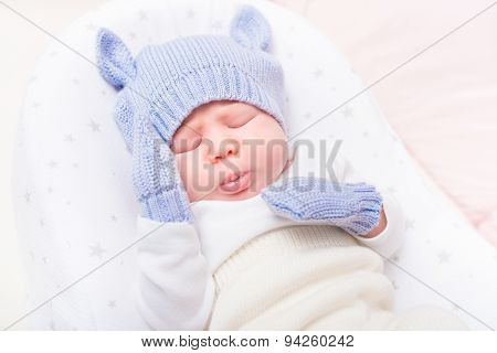 Sweet Little Baby Wearing Knitted Blue Hat With Ears And Mittens Lying In Beautiful Cradle