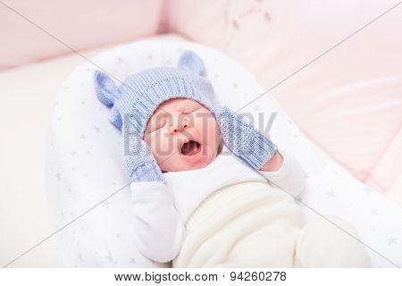 Yawning Little Baby Wearing Knitted Blue Hat With Ears And Mittens Lying In Beautiful Cradle